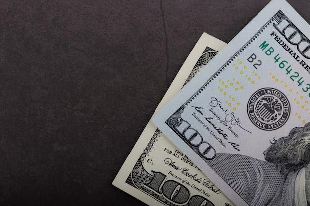 Cento banconote in dollari su una superficie grigia.