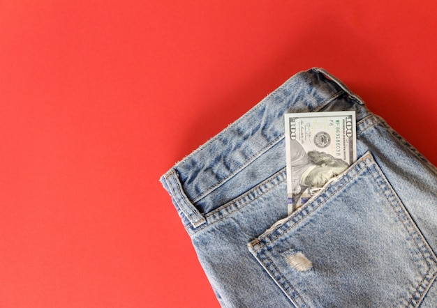 Cento dollari in tasca dei jeans sul rosso