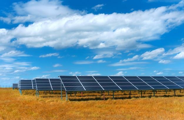 Centrale solare, pannelli solari blu sul campo di erba arancione di autunno sotto il cielo blu con nuvole. generazione di energia solare, produzione di energia rinnovabile