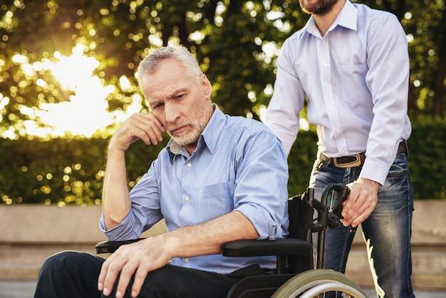 Centro di riabilitazione. l'uomo triste si siede in sedia a rotelle.