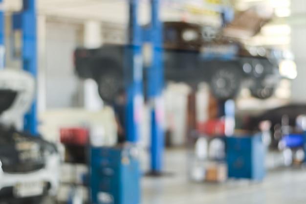 Centro di servizi di riparazione auto offuscato utilizzare noi sfondo di riparazione tecnico di manutenzione dell'automobile