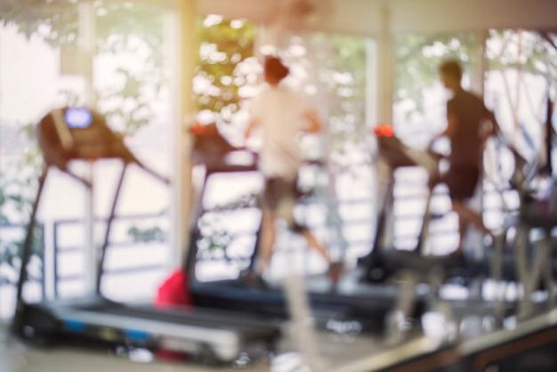 Centro fitness sfocato con macchine cardio e pesi, attrezzature per l'allenamento della forza. figure di umani che corrono su tapis roulant in palestra.
