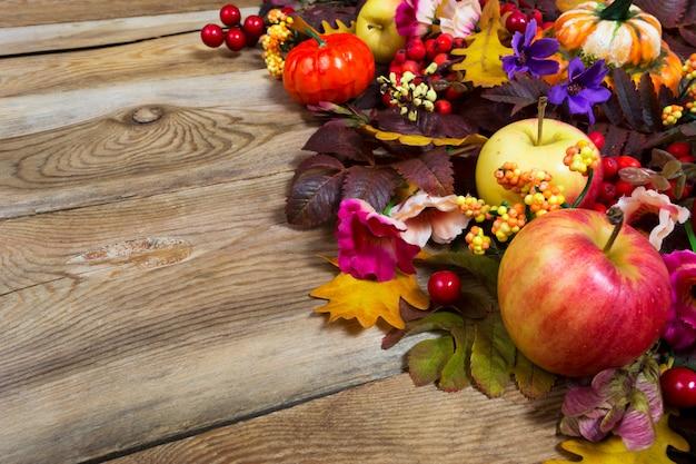 Centrotavola del ringraziamento con mele, foglie di autunno, fiori rosa e viola