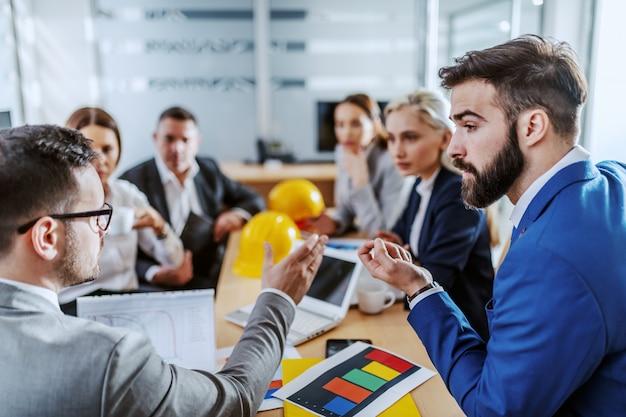 Ceo pensieroso seduto in sala riunioni con i suoi dipendenti e parlando dell'importanza del nuovo progetto.