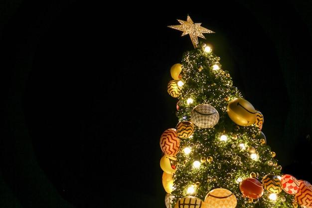 Cerchi la vista dell'albero di natale e decori con l'isolato principale di illuminazione sul nero.