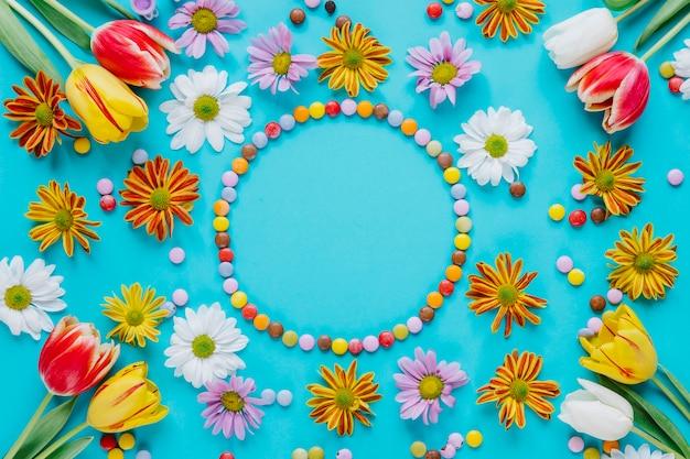 Cerchia di caramelle tra i fiori che sbocciano