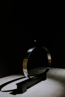 Cerchio di metallo di fronte a un muro nero