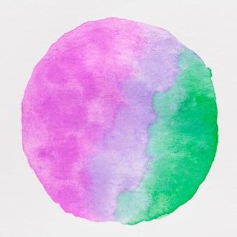 Cerchio fatto con vernice di colore di acqua viola e verde su sfondo bianco