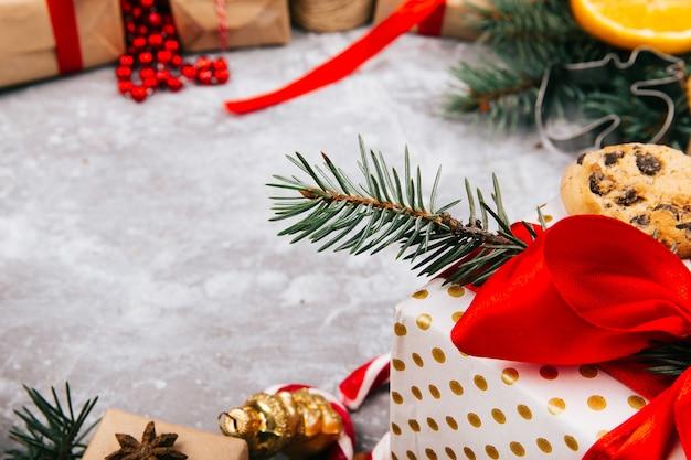 Cerchio fatto di arance, biscotti, rami di abete, scatole rosse presenti e altri tipi di decorazioni natalizie
