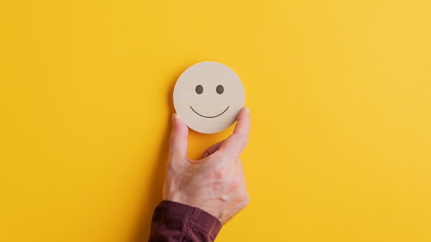 Cerchio in legno tagliato con la faccia sorridente su di esso
