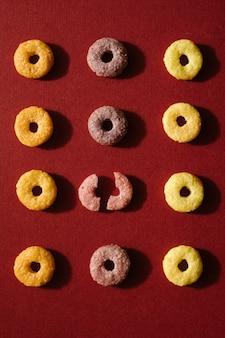 Cereale da prima colazione multicolore in un modello geometrico su fondo rosso. un cereale è rotto