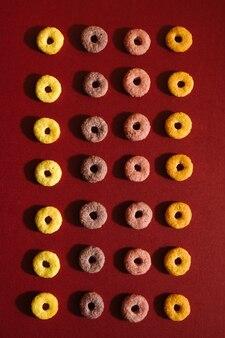 Cereale da prima colazione multicolore in un modello geometrico su fondo rosso