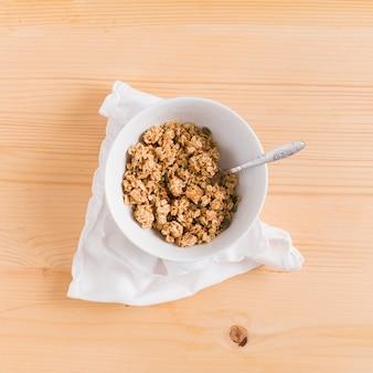 Cereale e cucchiaio della prima colazione del granoturco dell'avena nella ciotola bianca sopra il tovagliolo bianco sullo scrittorio di legno
