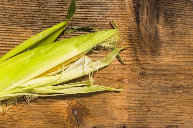 Cereale fresco sulla pannocchia contro fondo di legno