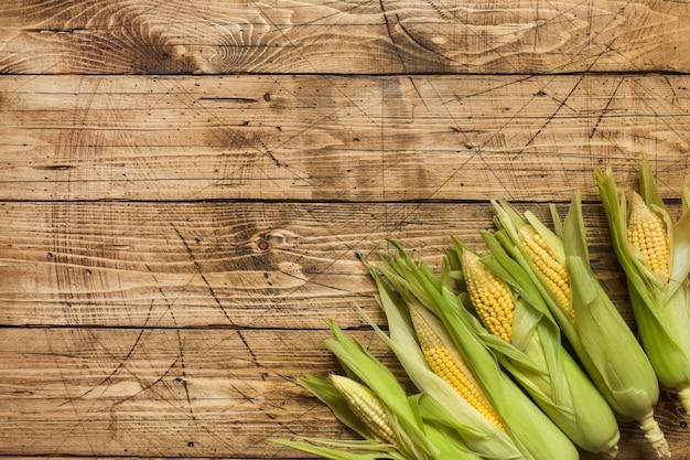 Cereale fresco sulle pannocchie sulla tavola di legno rustica