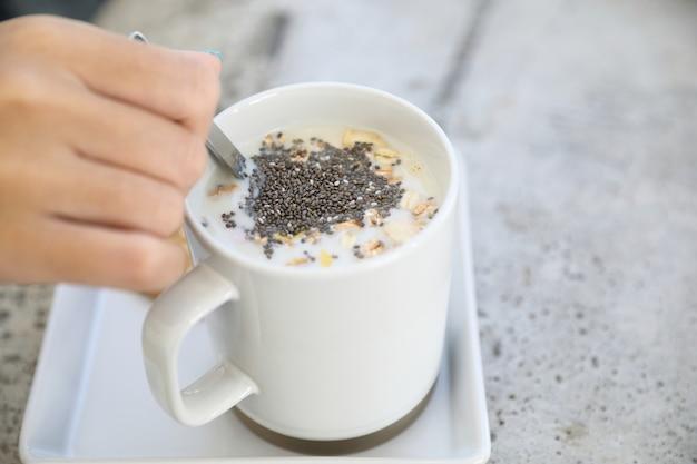 Cereale sul latte in tazza con la prima colazione della mano della donna