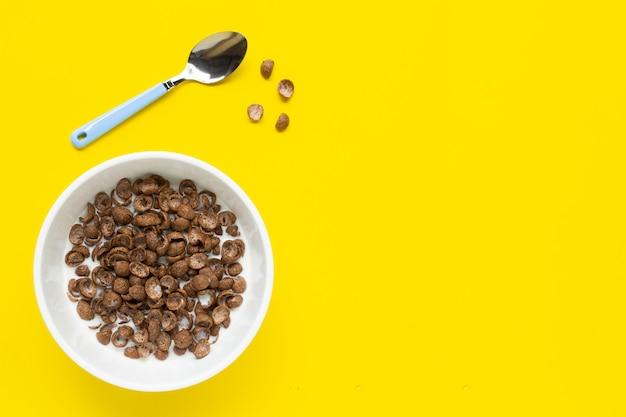 Cereali al cioccolato con latte su giallo.