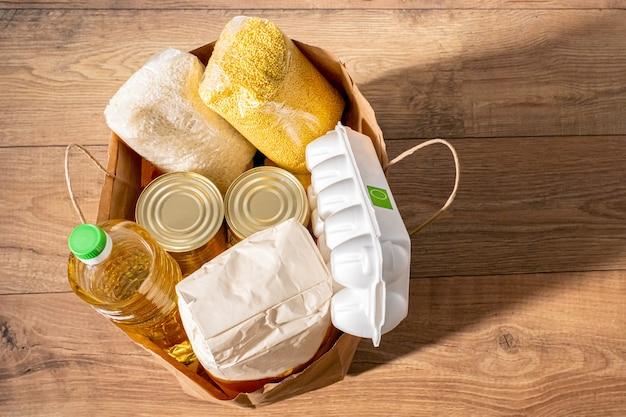 Cereali, cereali, olio, spezzatino, porridge e generi alimentari in scatola in una borsa artigianale per gli acquisti.
