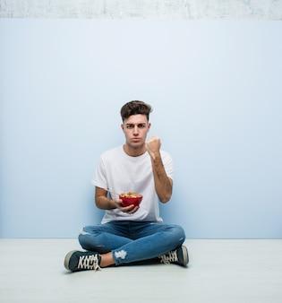 Cereali da mangiare giovane che si siedono sul pavimento che mostra pugno con con espressione facciale aggressiva.