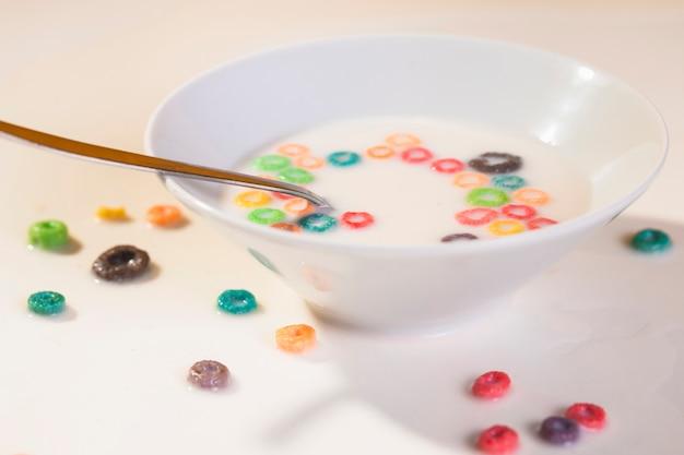 Cereali dell'angolo alto sulla tavola e sulla ciotola con i cereali