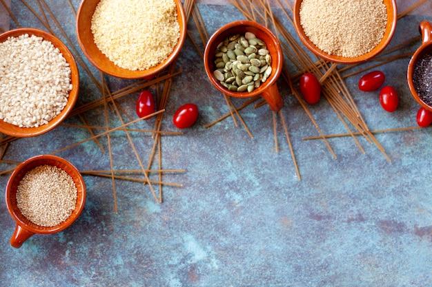 Cereali e semi in ciotole di ceramica e spaguetti integrali. cibo vegetariano . vista dall'alto. copia spazio