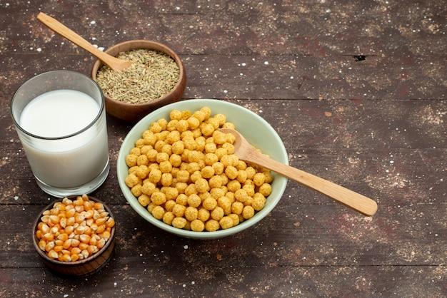 Cereali gialli di vista frontale dentro il piatto con latte freddo fresco su legno scuro, alimento dei cereali dei fiocchi di granturco della prima colazione