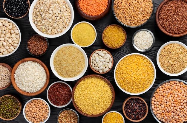 Cereali, granaglie, semi e semole su fondo di legno nero