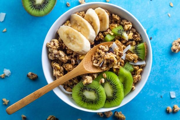 Cereali per la colazione a secco. ciotola croccante di muesli del miele con le fette di banana e di kiwi freschi su un fondo blu. cibo sano, fitness e fibra. vista dall'alto. ora di colazione