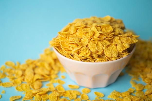 Cereali per la colazione in una ciotola rosa su sfondo blu.