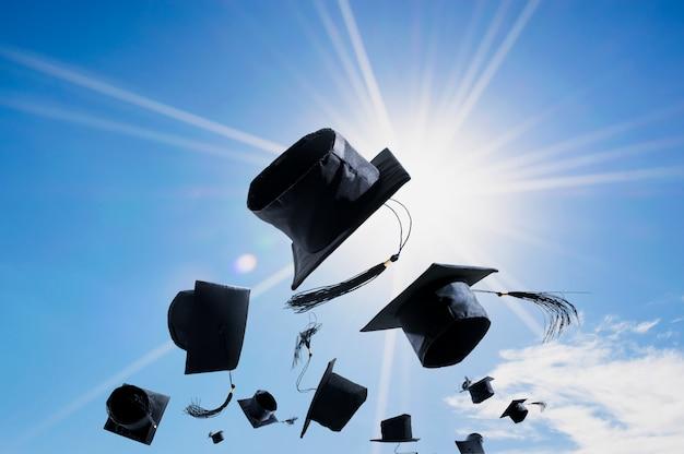 Cerimonia di laurea, tappi di laurea, cappello gettato in aria con estratto di cielo blu.