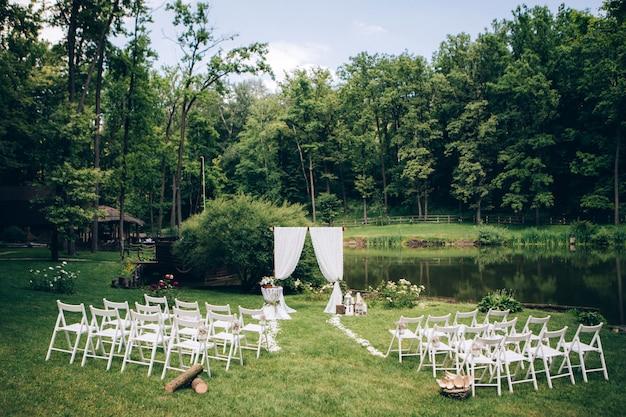 Cerimonia di nozze in uscita. decor studio. sedie di legno bianche su un prato verde. arco festivo di nozze poltrone bianche per gli ospiti