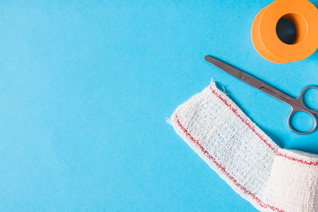 Cerotto adesivo e garza di cotone benda con forbici su sfondo blu