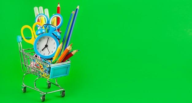 Cestino con materiale scolastico su un verde