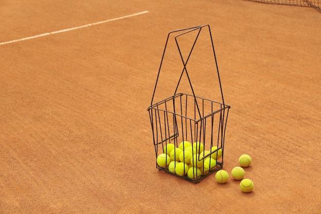 Cestino con palline da tennis su campo in terra battuta