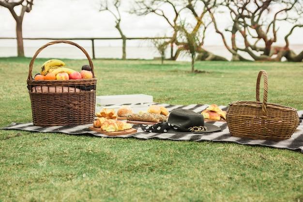 Cestino da picnic con pane cotto e cappello sulla coperta