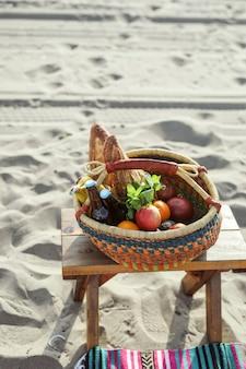 Cestino da picnic pieno di snack e bevande in spiaggia