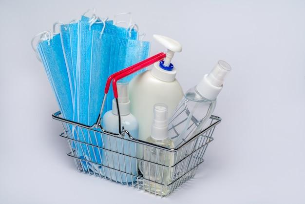 Cestino del supermercato con mascherina medica protettiva e una bottiglia di disinfettante per mani gel per alcool. concetto di acquisto di coronavirus su sfondo grigio chiaro