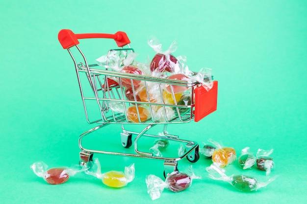 Cestino del supermercato, dentro confetti multicolore al caramello.