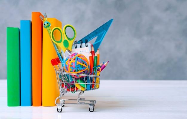 Cestino della spesa variopinto dei rifornimenti di scuola grigio con uno spazio del testo della copia.