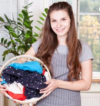 Cestino di lavanderia di trasporto della donna felice nella stanza della cucina