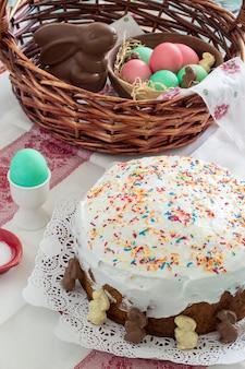 Cestino di pasqua con uova colorate, coniglio di cioccolato, torta di pasqua - kulich