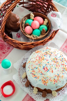 Cestino di pasqua con uova colorate, coniglio di cioccolato, torta di pasqua
