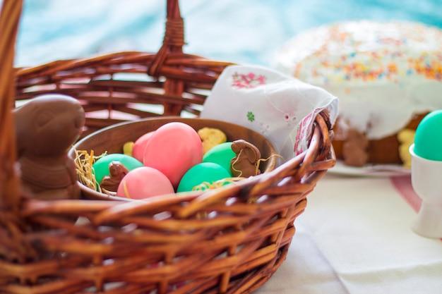 Cestino di pasqua con uova colorate, coniglio di cioccolato
