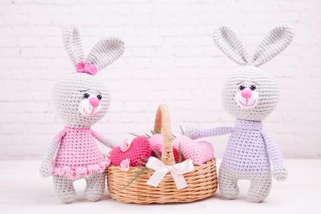 Cestino di vimini con cuori in maglia multicolore. coniglio lavorato a maglia arredamento festivo san valentino. giocattolo lavorato a mano, amigurumi