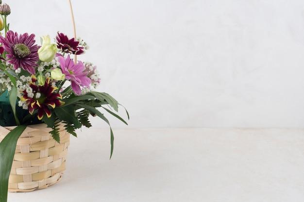 Cestino di vimini con fiori su sfondo grigio