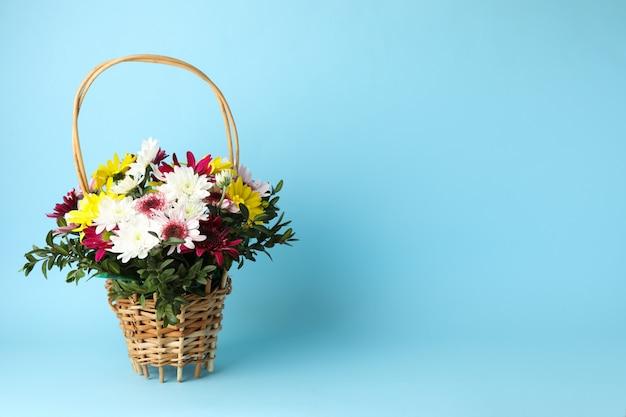 Cestino di vimini con i fiori sull'azzurro