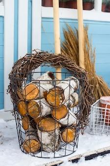 Cestino di vimini di metallo con legno di betulla accanto agli attrezzi da giardino al muro di una casa di campagna blu