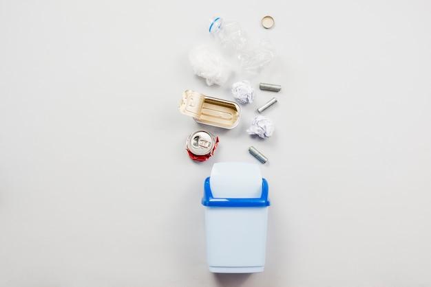 Cestino riciclabile che cade nel bidone