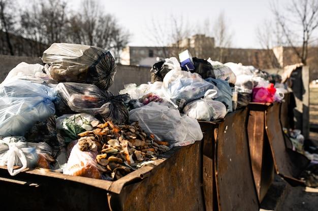 Cestino traboccante. i bidoni dell'immondizia sono troppo pieni di pacchetti con rifiuti