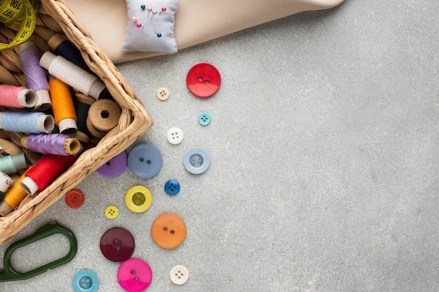 Cestino vista dall'alto con fili per cucire e bottoni